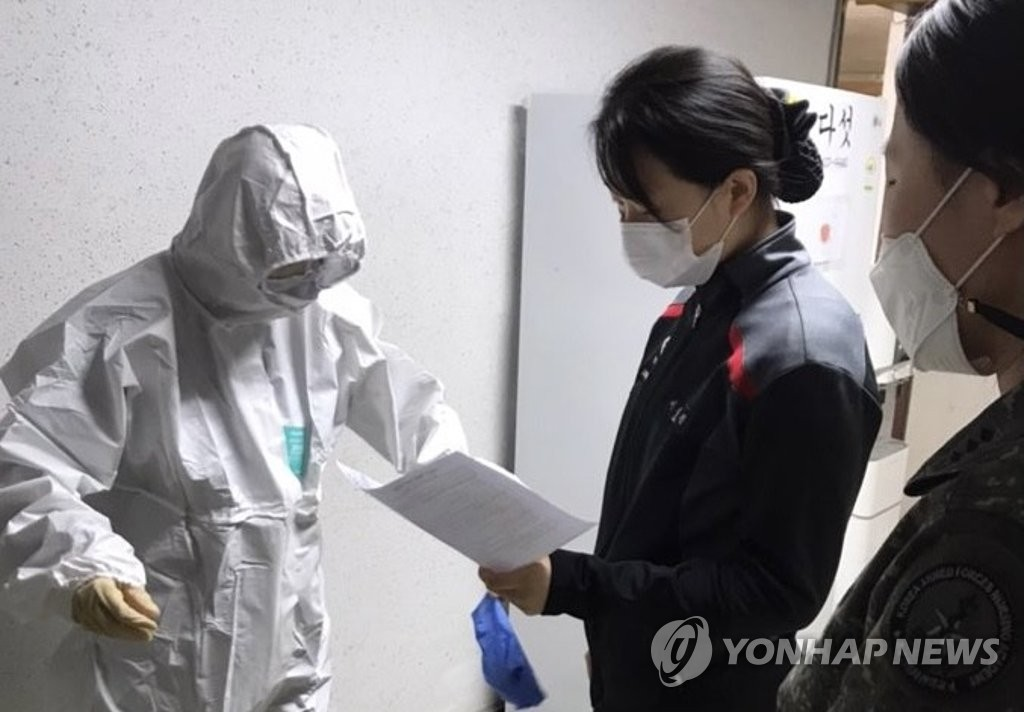 In this photo provided by the defense ministry on Dec. 18, 2020, a military nursing academy cadet (L) puts on protective gear. (PHOTO NOT FOR SALE) (Yonhap)
