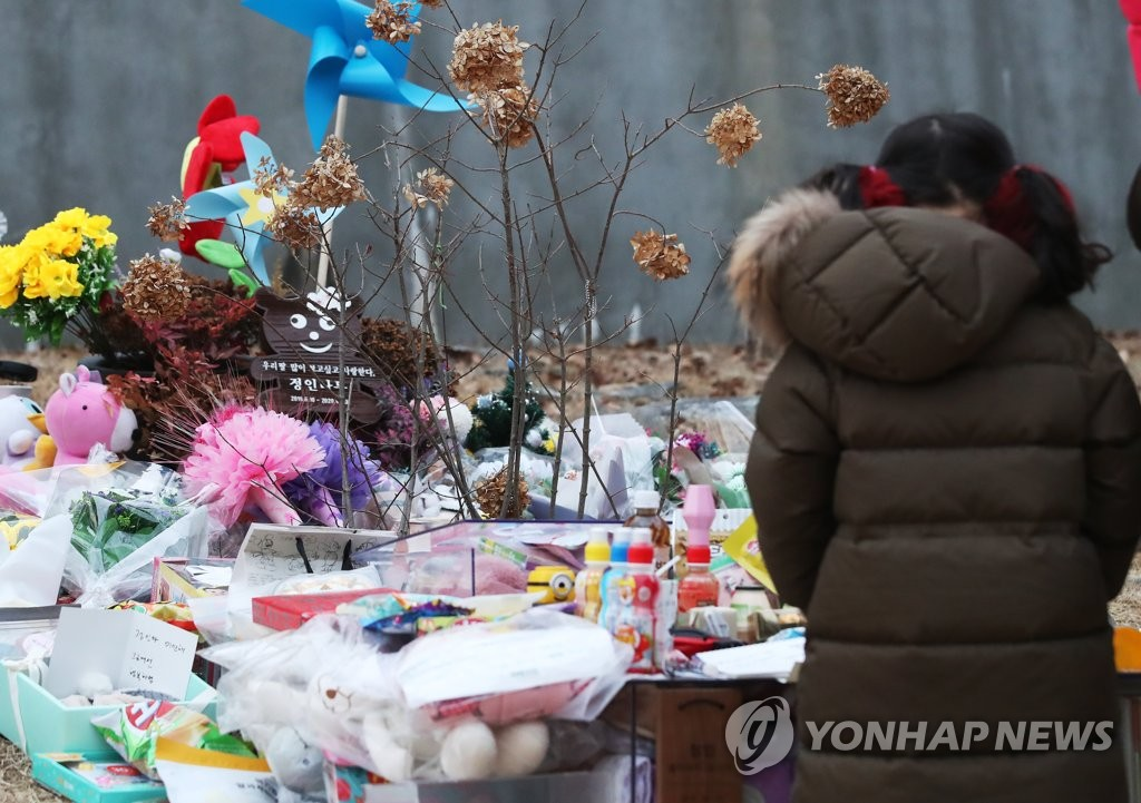 A child pays tribute to a 16-month-old girl, who died in October after alleged abuse by her adoptive parents, in a cemetery in Yangpyeong, east of Seoul, on Jan. 4, 2021. (Yonhap)