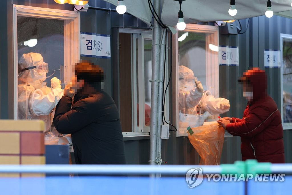 Medical workers collect specimen from people at a temporary COVID-19 screening station on Jan. 6, 2021. (Yonhap)
