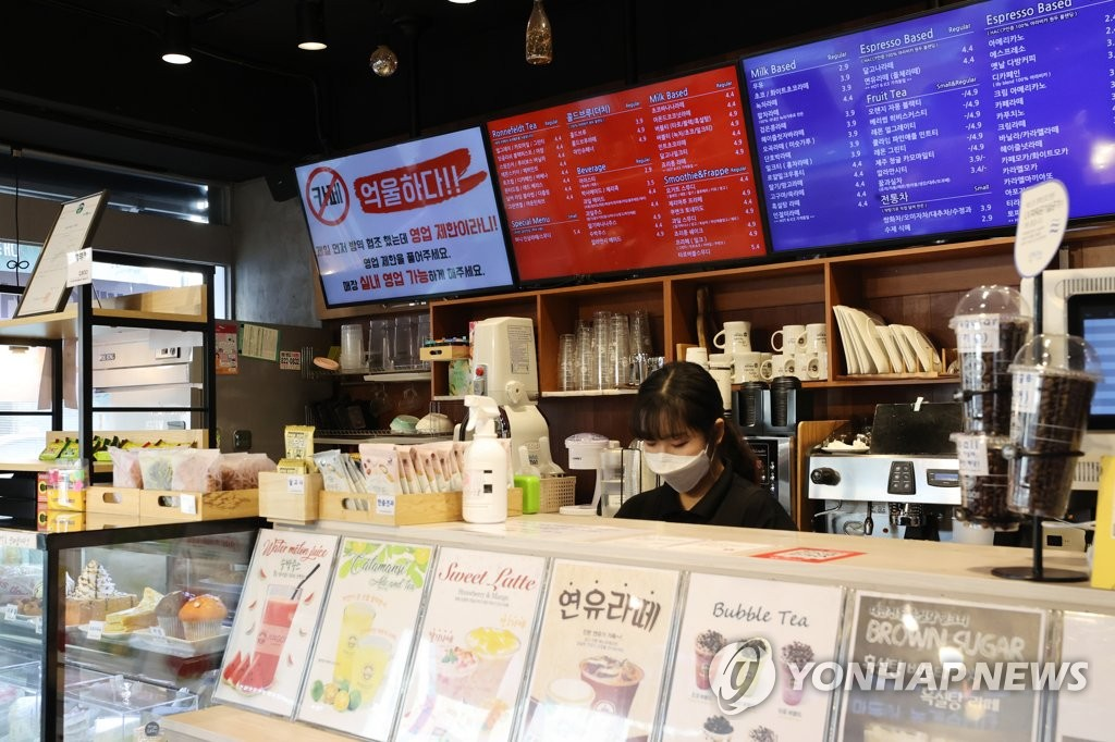 This file photo shows a sign (top left) criticizing the government's COVID-19 business restrictions at a cafe in southern Seoul on Jan. 6, 2021. (Yonhap)