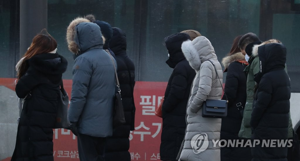 People go to work in thick coats near Gwanghwamun in Seoul on Jan. 8, 2021. (Yonhap)