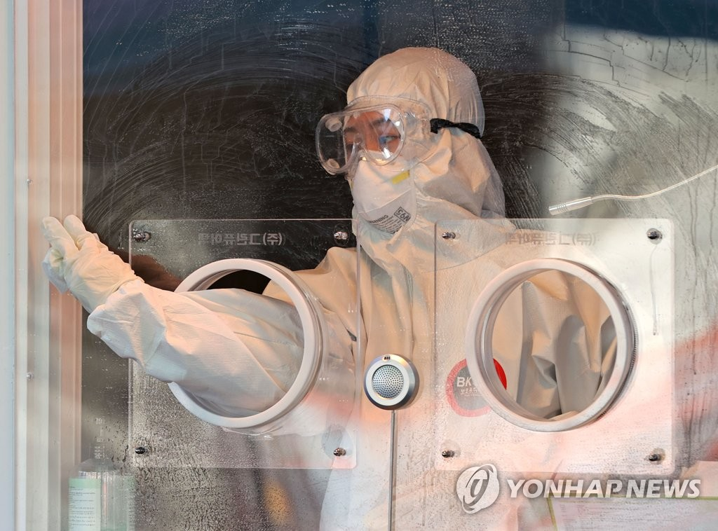 A medical worker cleans a temporary COVID-19 screening station set up in front of Seoul Station on Jan. 16, 2021. (Yonhap)