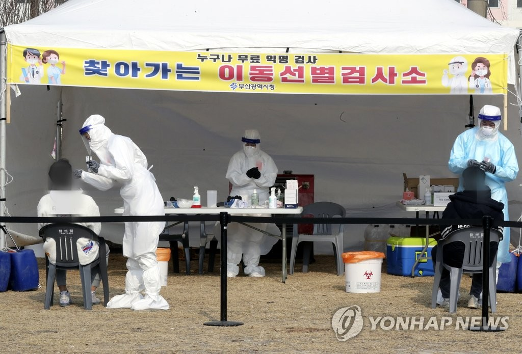 This photo taken on Jan. 18, 2021, shows health workers clad in protective suits working at a makeshift virus testing clinic in Busan. (Yonhap)