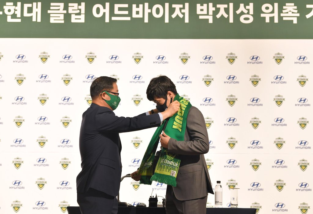 Former South Korean men's national football captain Park Ji-sung (R) puts on a muffler for Jeonbuk Hyundai Motors before being introduced as the K League 1 club's new adviser in Goyang, Gyeonggi Province, on Jan. 21, 2021, in this photo provided by Jeonbuk. (PHOTO NOT FOR SALE) (Yonhap)