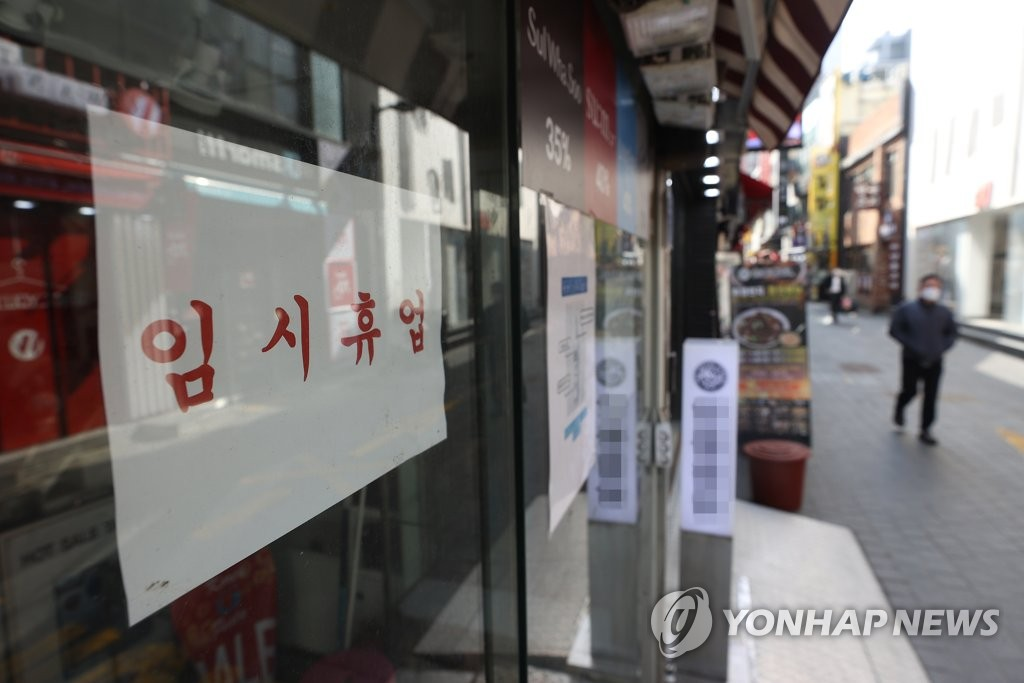 This file photo, taken March 3, 2021, shows a sign announcing a temporary closure due to the pandemic that was put up at a shop in Seoul's shopping district of Myeongdong. (Yonhap)