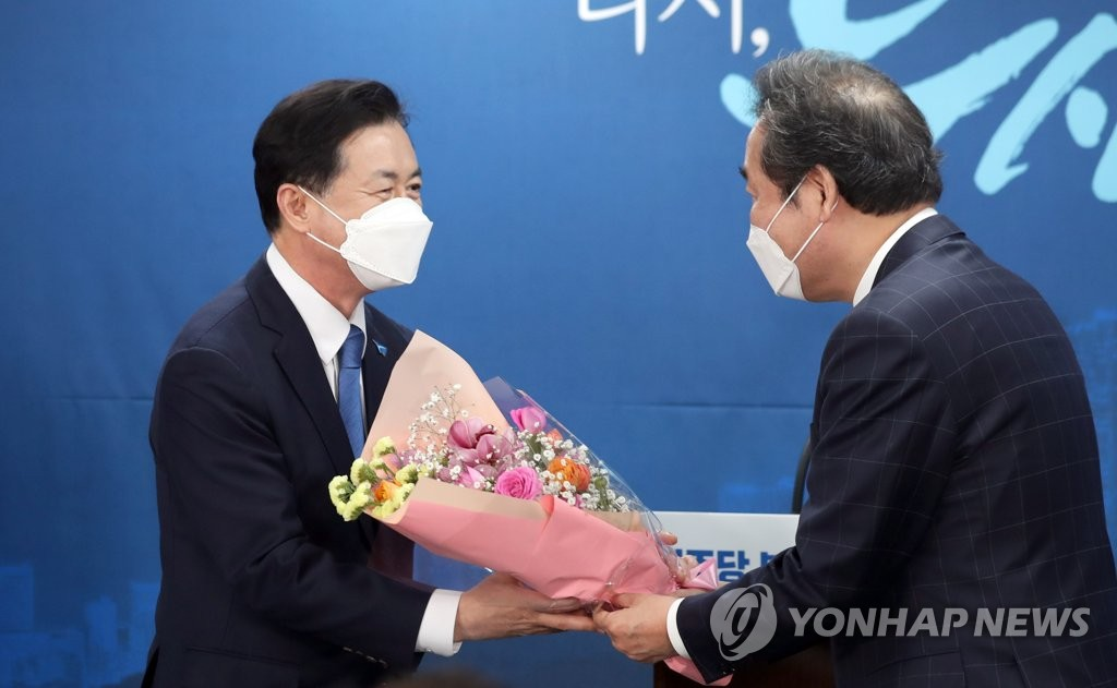 Former Oceans Minister Kim Young-choon (L) receives a bouquet of flowers from Democratic Party (DP) Chairman Lee Nak-yon in Busan, 450 kilometers southeast of Seoul, on March 6, 2021, after being named the DP's candidate for Busan mayoral by-election. (Yonhap)