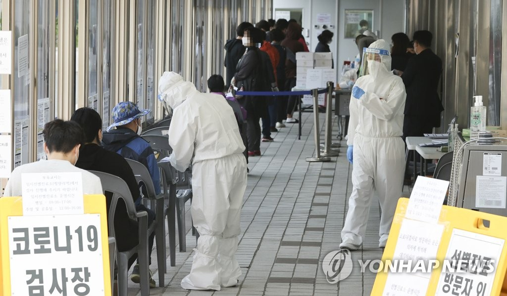Citizens wait in a line to receive COVID-19 tests at a makeshift clinic in eastern Seoul on April 7, 2021. (Yonhap)