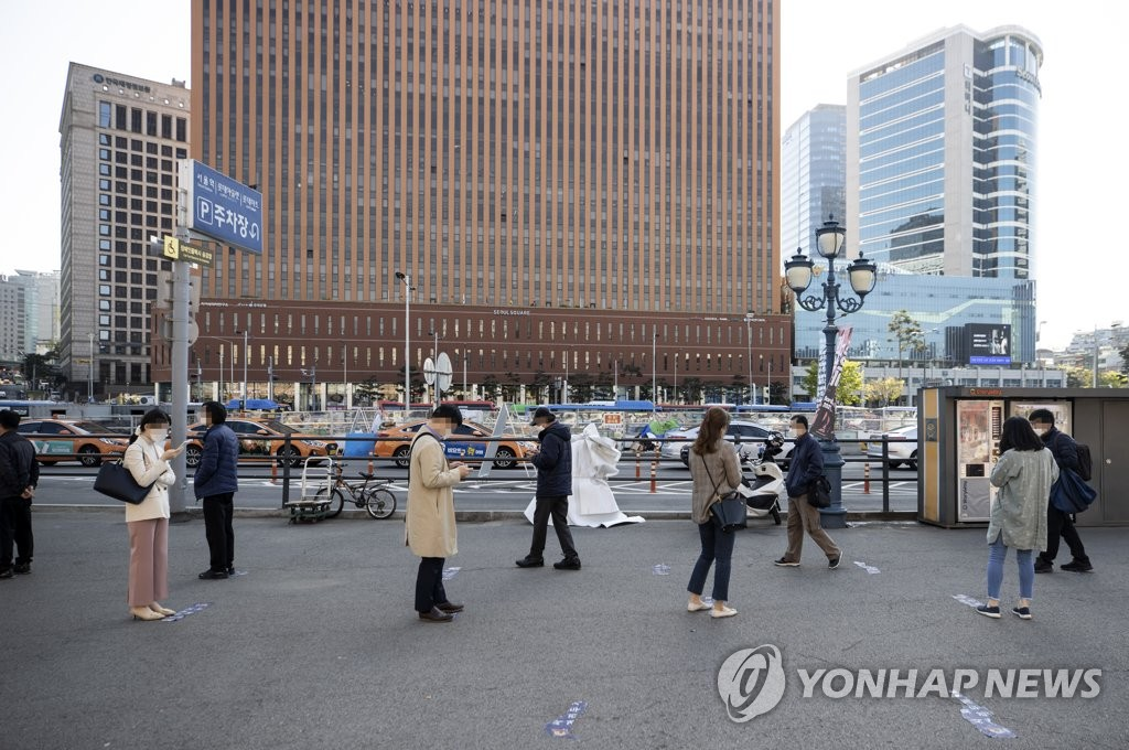 Citizens wait in a line to receive COVID-19 tests in central Seoul on April 8, 2021. (Yonhap)