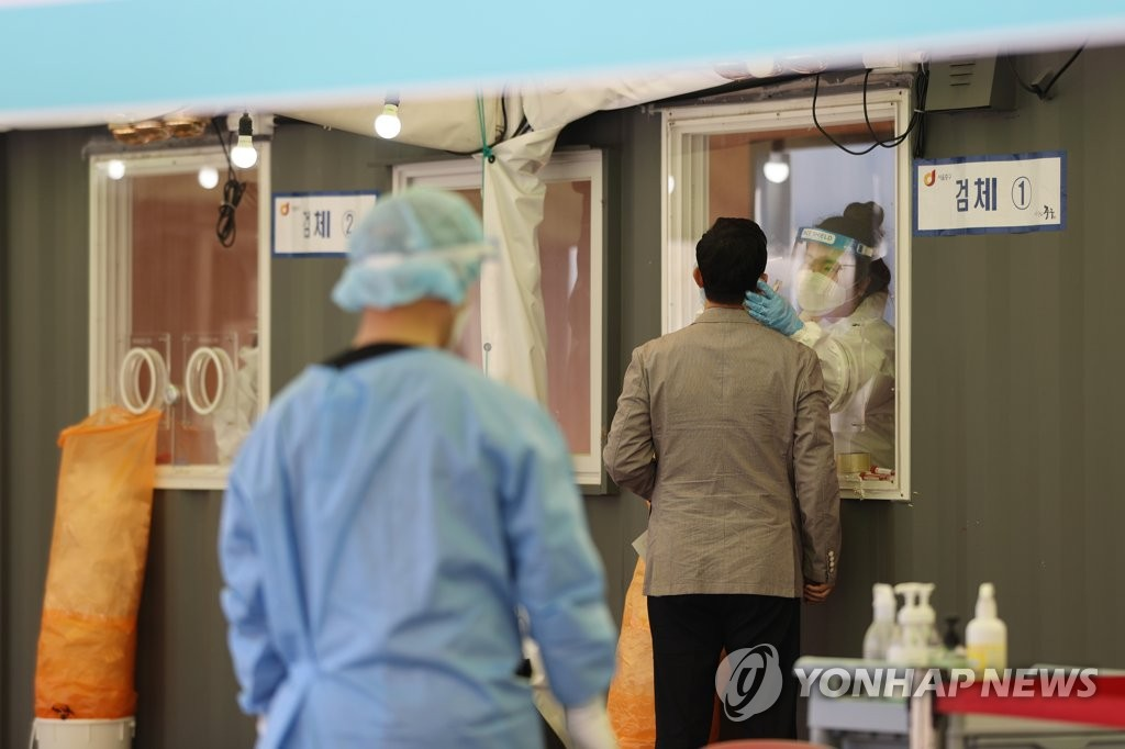 Visitors receive COVID-19 tests at a makeshift clinic in central Seoul on April 9, 2021. (Yonhap)