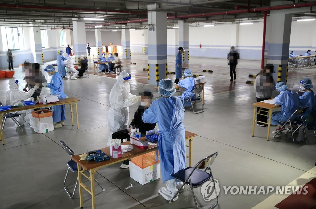 This photo taken on April 21, 2021, shows health workers clad in protective suits conducting tests on citizens at a makeshift virus testing clinic set up in a church's parking lot in Gwangju. (Yonhap)
