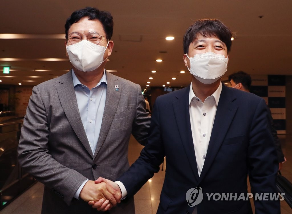 Rep. Song Young-gil (L), head of the ruling Democratic Party, and Lee Jun-seok, chairman of the main opposition People Power Party, shake hands after holding a meeting at a restaurant in Seoul on July 12, 2021. (Yonhap)