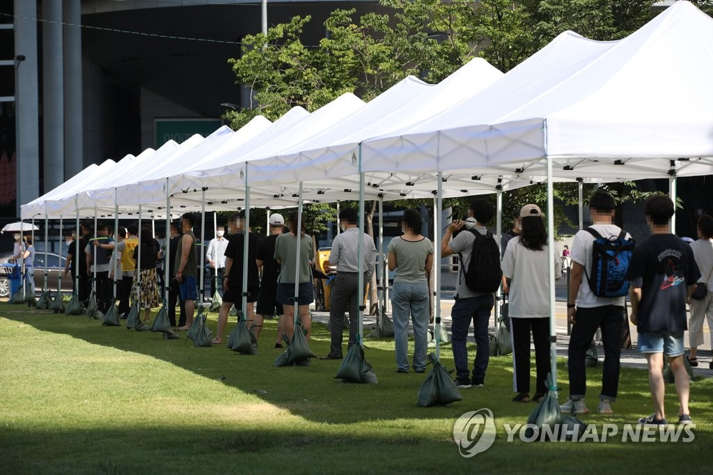 People stand in line to get COVID-19 tests at a screening center in front of Yongsan Station in Seoul on July 20, 2021. (Yonhap)