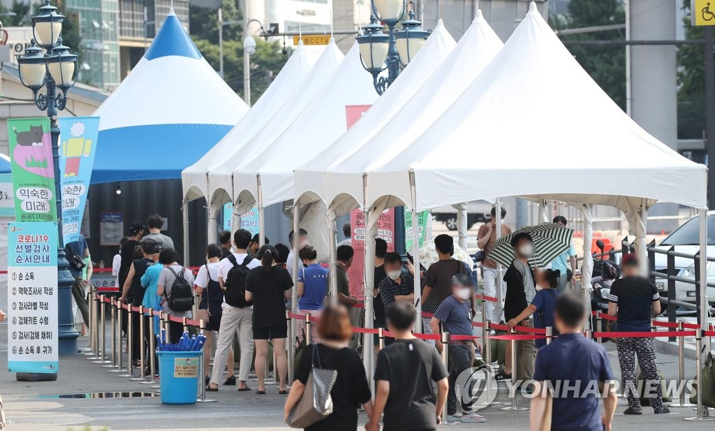 People wait in line to receive COVID-19 tests at a makeshift virus testing clinic in Seoul on July 28, 2021. (Yonhap)