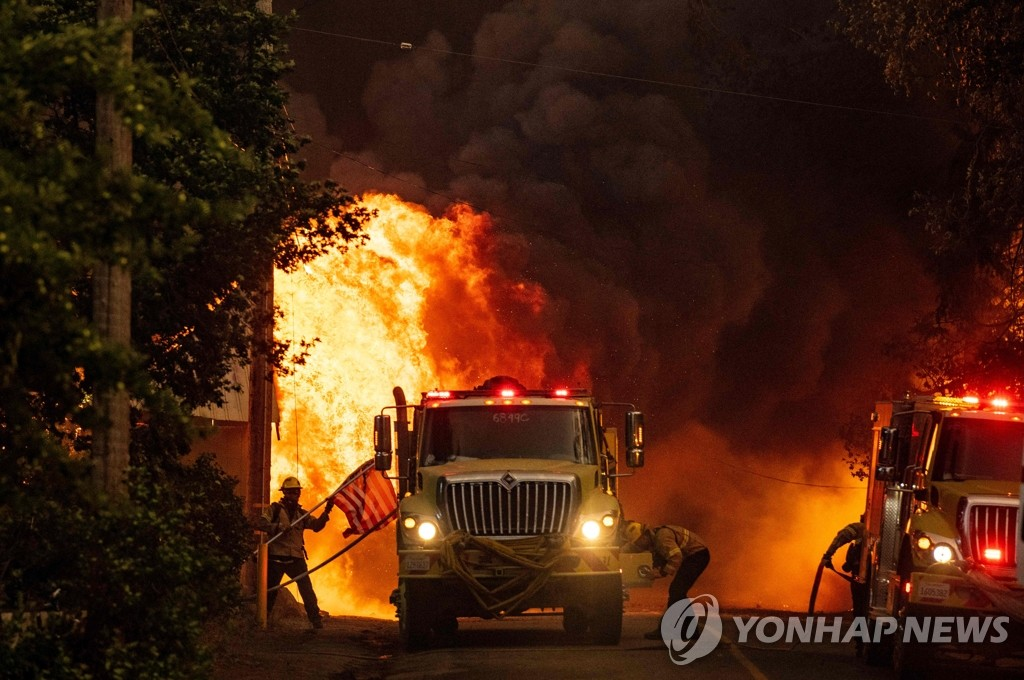 지난 4일 캘리포니아주 플러머스 카운티 국유림 인근 그린빌에서 한 소방관이 불타는 가옥에 걸려있던 성조기를 수습하고 있다. [AFP=연합뉴스 자료사진]