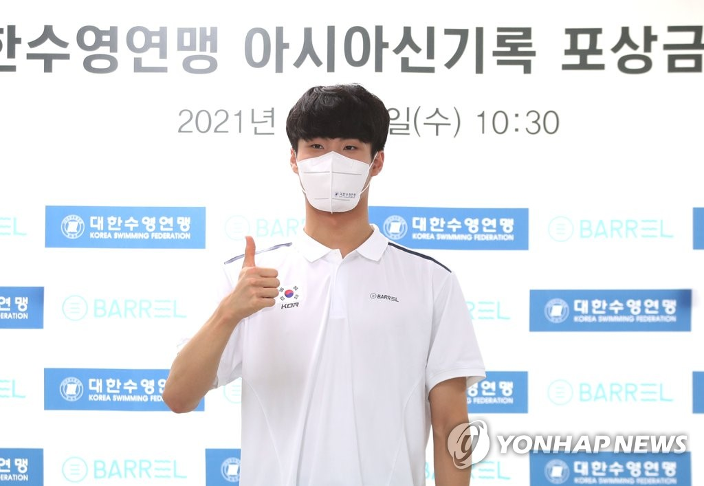 South Korean swimmer Hwang Sun-woo poses for photos after receiving prize money from the Korea Swimming Federation in a ceremony in Seoul on Aug. 11, 2021. (Yonhap)