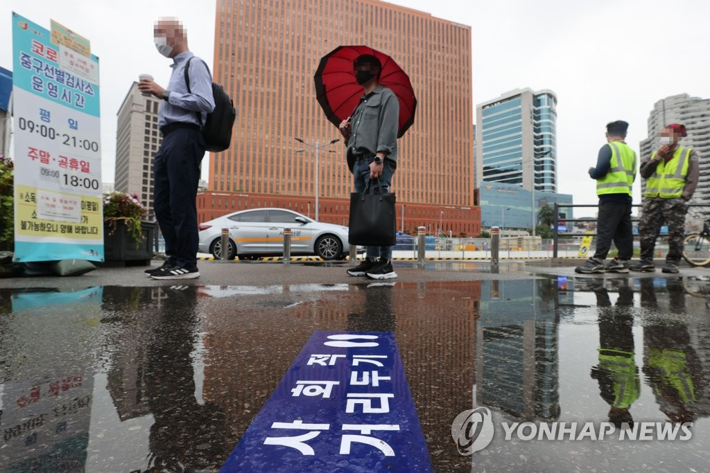 This photo taken on Aug. 18, 2021, shows people waiting to take a coronavirus test at a makeshift testing center near Seoul Station in central Seoul. (Yonhap)