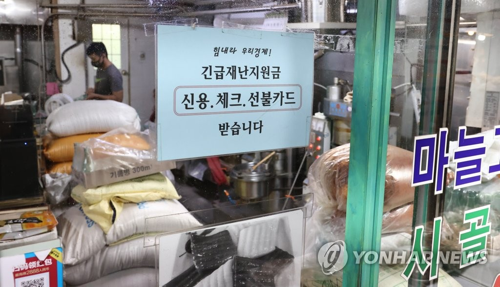 This photo, taken Aug. 26, 2021, shows a sign about the use of emergency cash handouts at a store in a traditional market. (Yonhap)